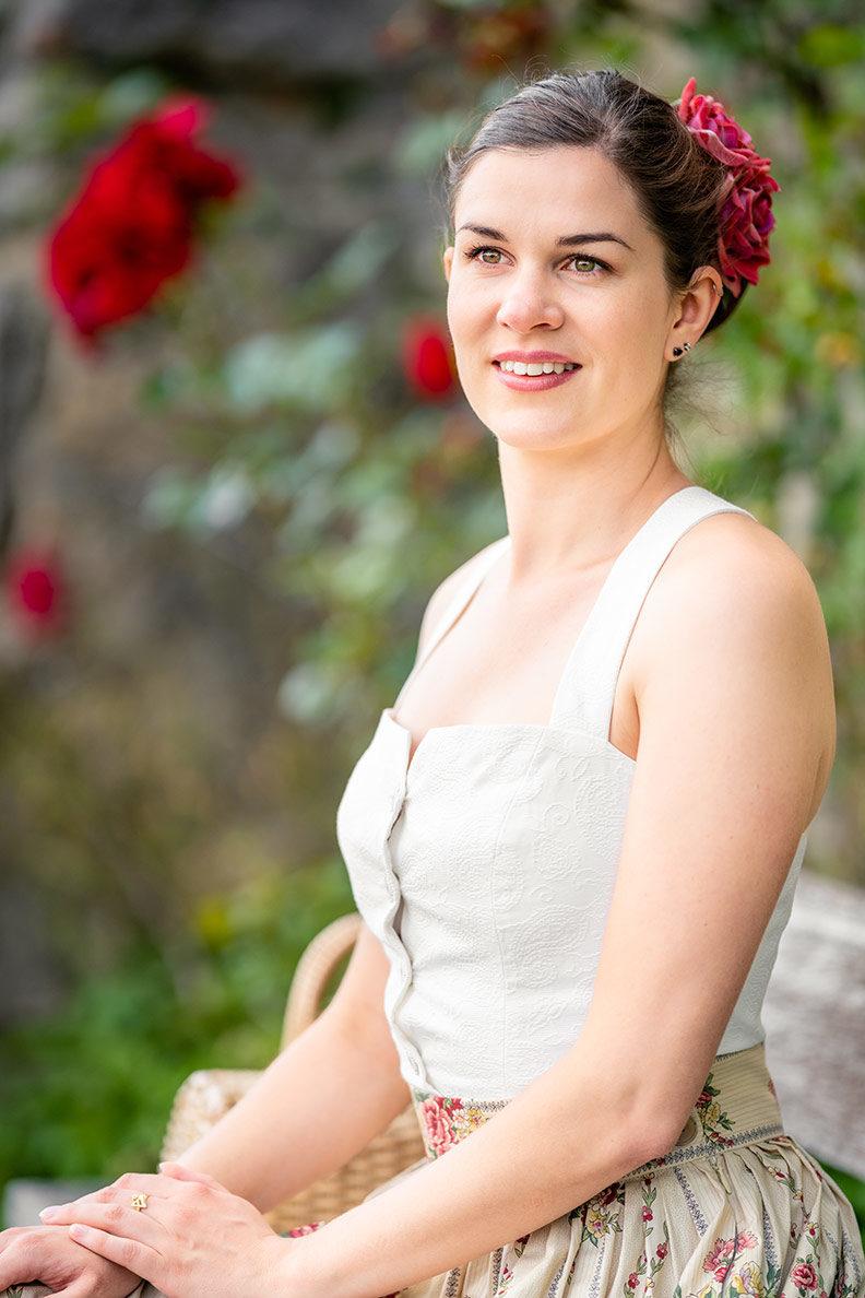RetroCat mit Rosenrock, weißem Top und Haarblume auf einer Bank