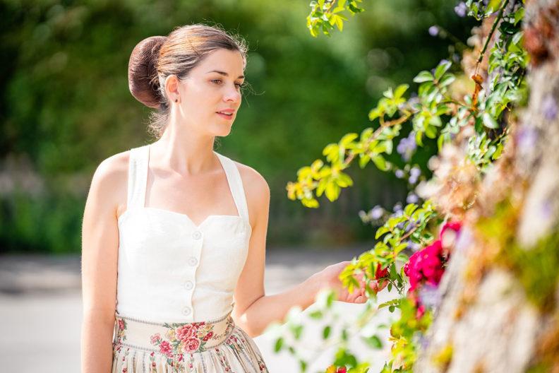 RetroCat mit einem Mieder-Top von Lena Hoschek vor einer Mauer mit Rosen