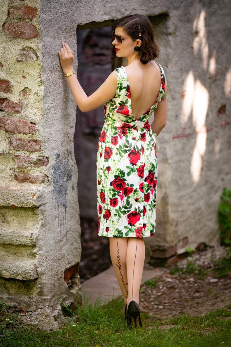 RetroCat in einem Kleid mit Rosenmuster und tiefem Rückenausschnitt