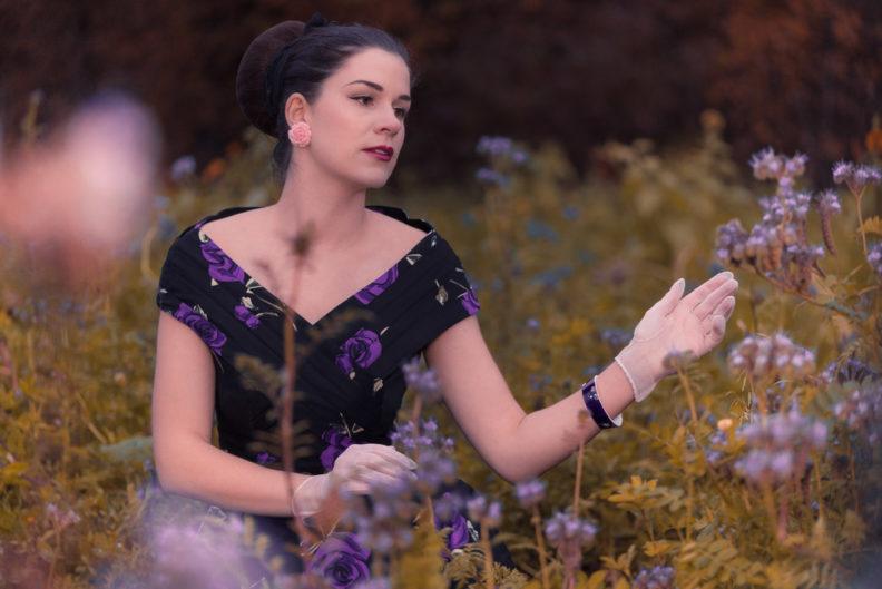 RetroCat in einem Retro-Kleid mit lila Rosen im Blumenfeld