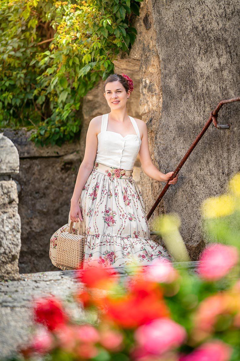 RetroCat mit Rosenrock, romantischem Top und Korbtasche auf dem Land