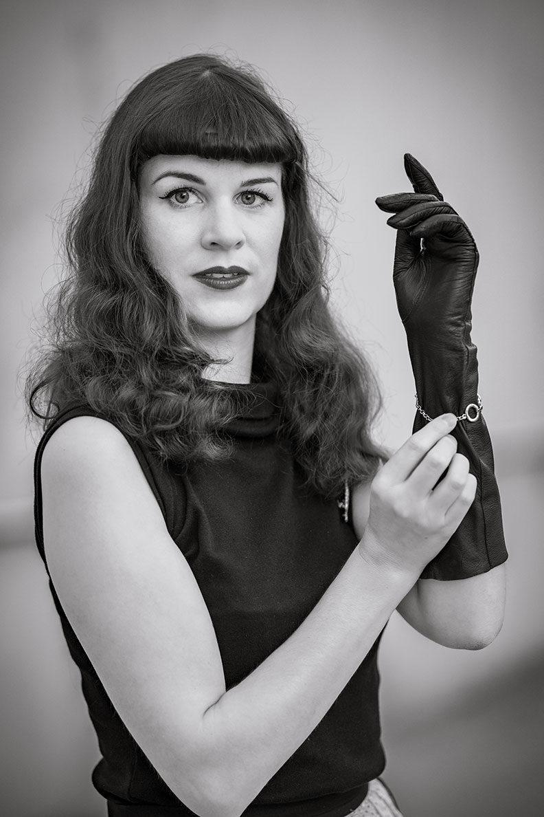 RetroCat mit Vintage-Lederhandschuhen und einem funkelnden Armband