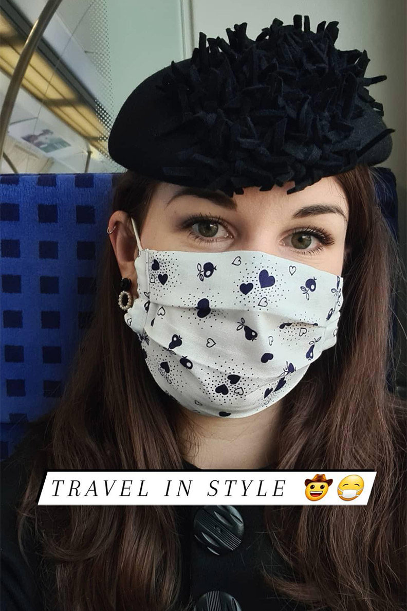 RetroCat wearing a hat and mask while she is in a train