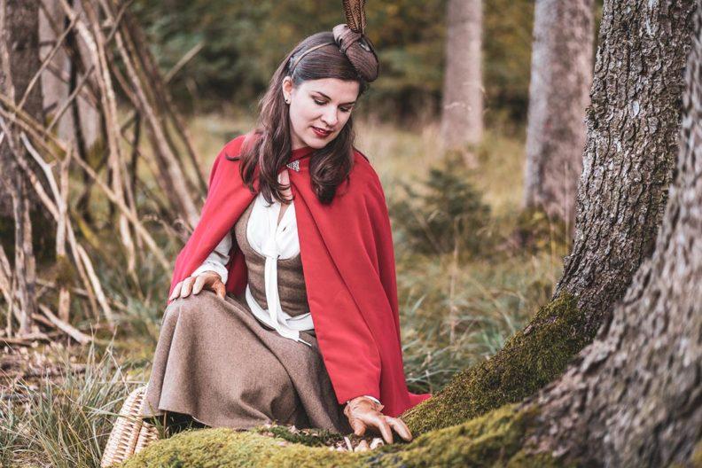 Rotkäppchen-Look: RetroCat mit rotem Cape, Fascinator und Tellerrock im Wald