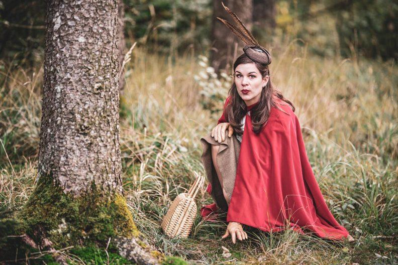 Rotkäppchen-Look: RetroCat mit Cape und Korbtasche im Wald