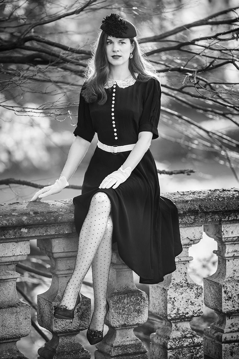 RetroCat wearing a little black dress, nylons, hat and retro accessories