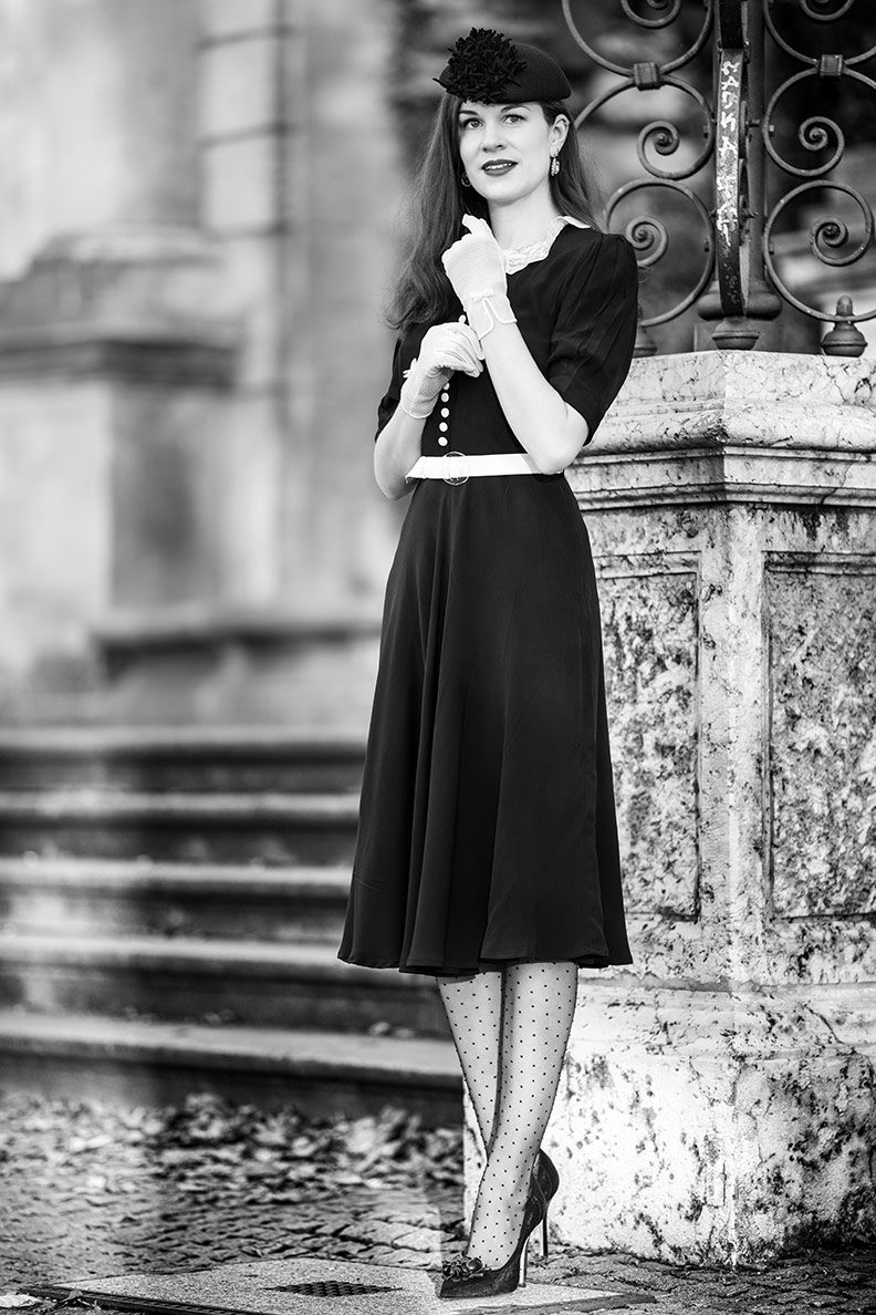 RetroCat wearing a little black dress with a white lace collar and matching gloves