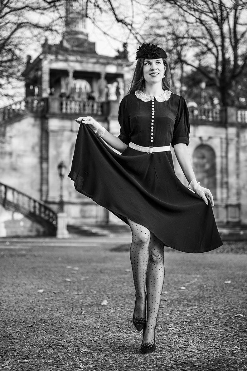 RetroCat mit schwarzem Retro-Kleid, gepunkteten Nylons und Vintage-Accessoires in München