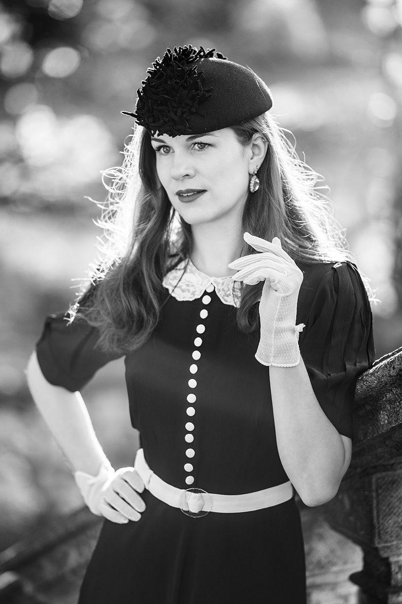 RetroCat im schwarzen Kleid mit weißem Spitzenkragen und passenden Handschuhen