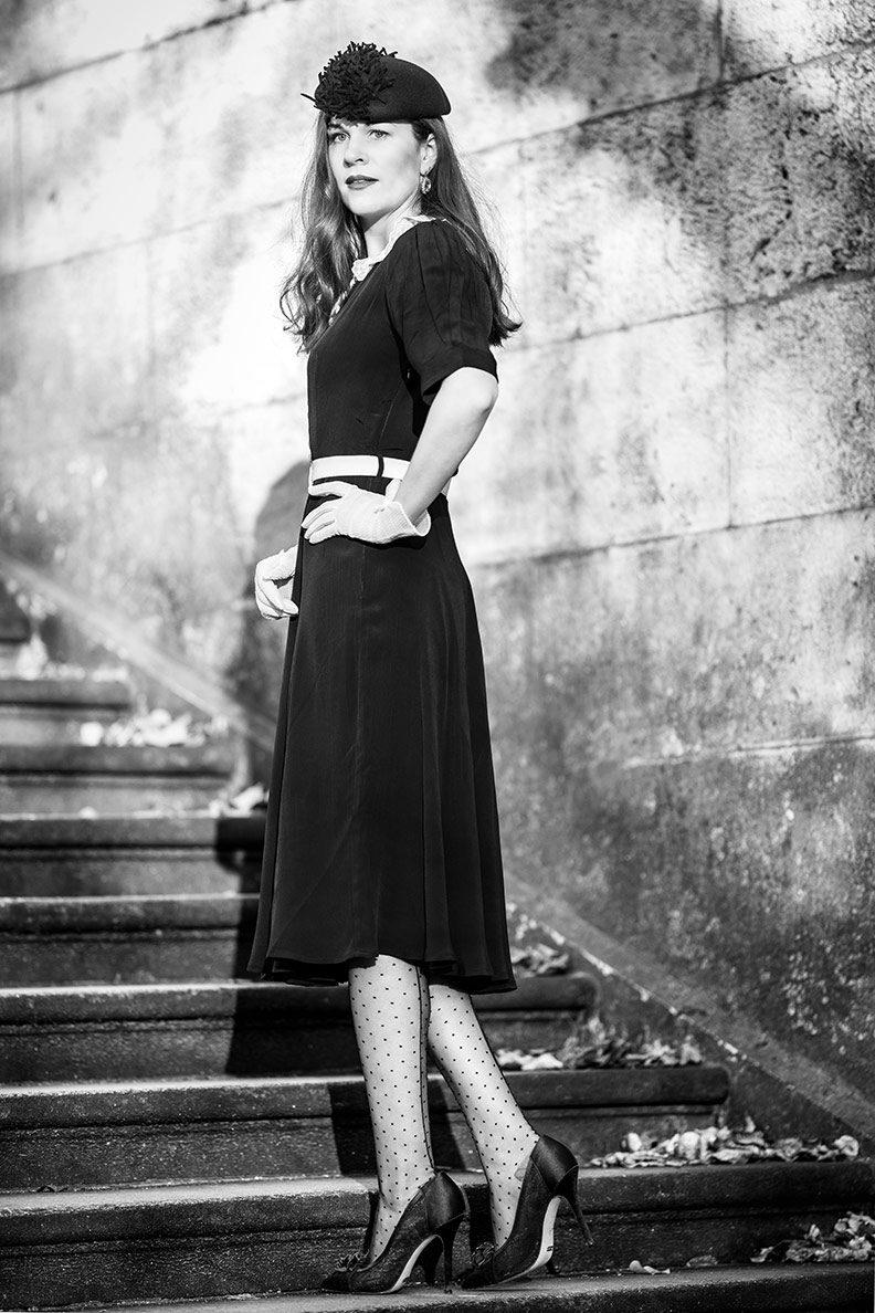 RetroCat wearing a black dress, nylon stockings, hat and gloves