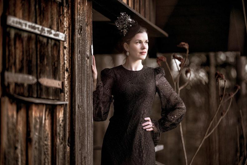 RetroCat in einem schwarzen Spitzenkleid von The Vampire's Wife x H&M vor einer Hütte