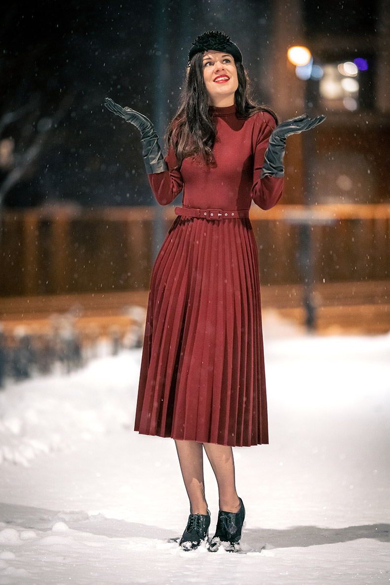 RetroCat trägt ein rotes Winterkleid und schwarze Handschuhe im Schnee
