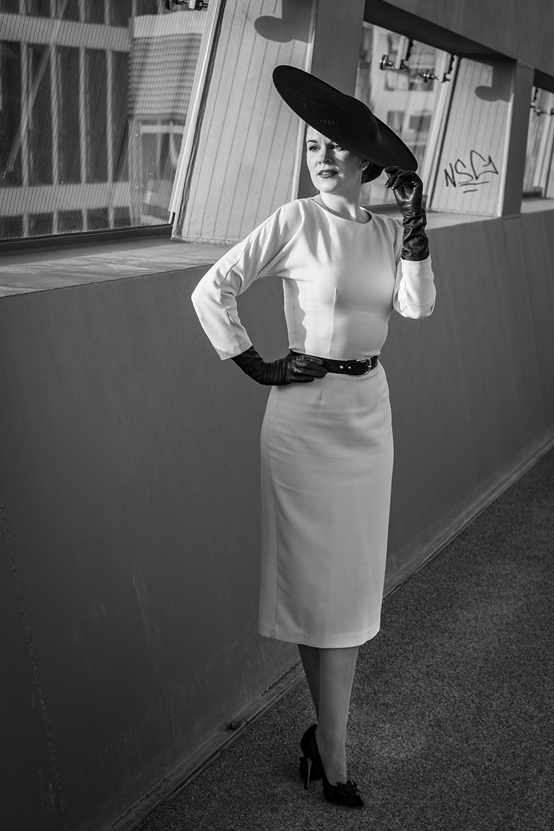 RetroCat wearing a white pencil dress and black retro accessories