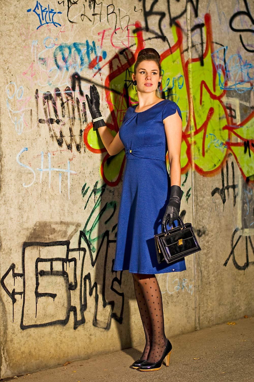 RetroCat mit einem blauen Kleid im 60er-Jahre-Stil und passenden Strumpfhosen