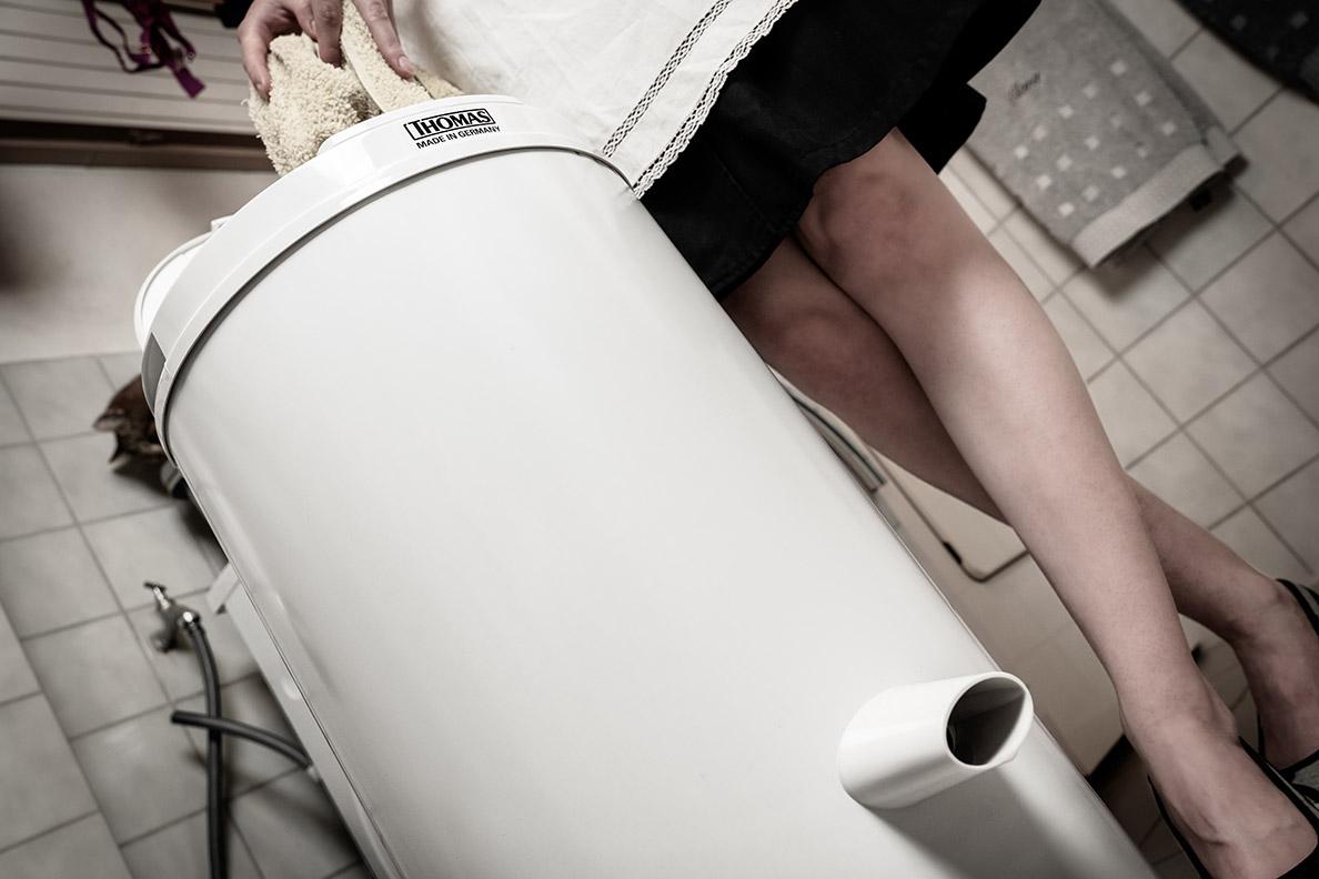 RetroCat beim Befüllen einer Wäscheschleuder mit einem nassen Handtuch