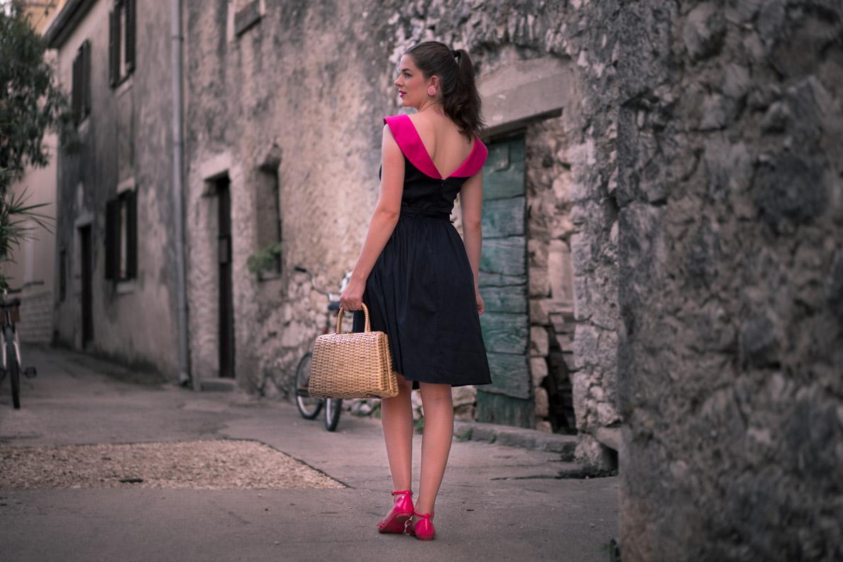 RetroCat trägt ein Sommerkleid mit pinkem Kragen und farblich passende, flache Sandalen