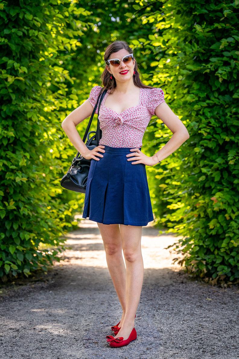 RetroCat trägt blaue Retro-Shorts zu einer Bluse von Lena Hoschek